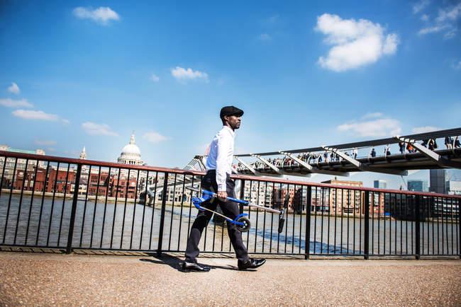 Homme d'affaires portant scooter, Millennium Bridge, Londres, Royaume-Uni — Photo de stock