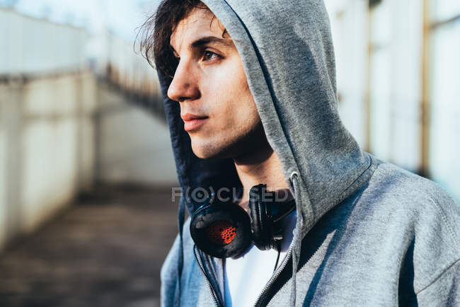 Portrait of man wearing hooded top and headphones looking away — Stock Photo