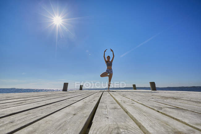 Mid distant view of woman on pier, standing on one leg arms raised — Stock Photo