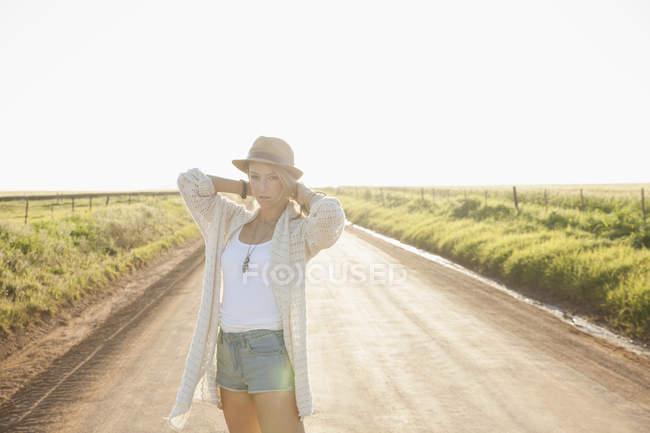 Середині дорослу жінку на сільська дорога, руки за шию, дивлячись на камеру — стокове фото