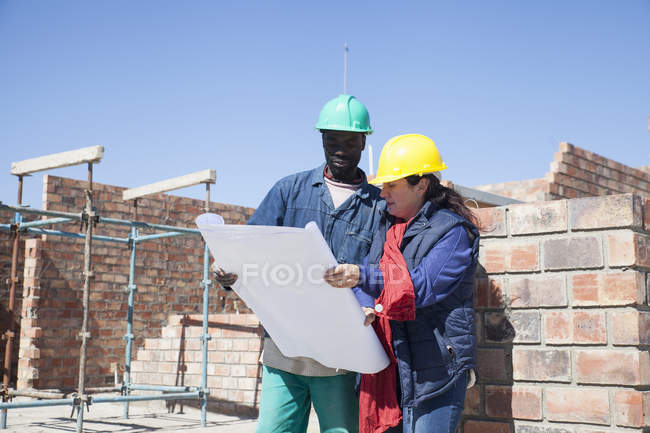 Site manager and builder looking at blueprint on construction site — Stock Photo