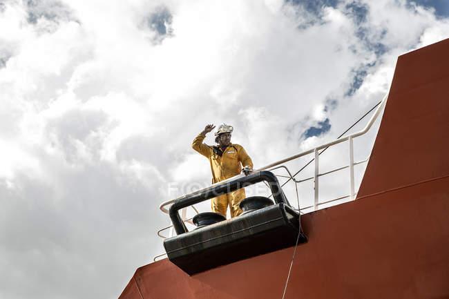 Рабочий причаливает нефтяной танкер на палубе, жестикулируя руками — стоковое фото