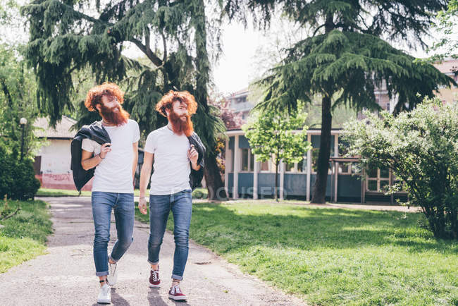 Young male hipster twins with red beards strolling in park — Stock Photo
