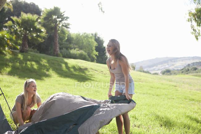 Dois amigos fêmeas jovens desembrulhar tenda — Fotografia de Stock