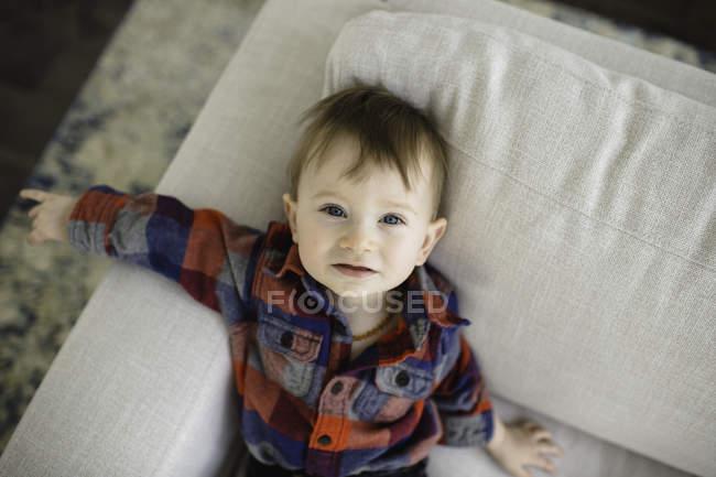 Портрет чоловічого Малюк лежить на дивані, шукаючи — стокове фото