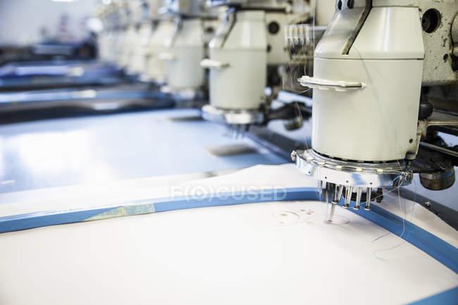 Linhas de máquinas de bordar programado velocidade costura pano branco na fábrica de roupas — Fotografia de Stock