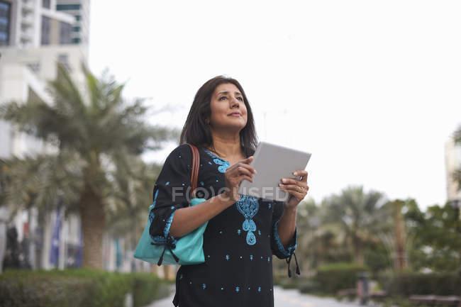 Mature businesswoman holding digital tablet in city, Dubai, United Arab Emirates — Stock Photo