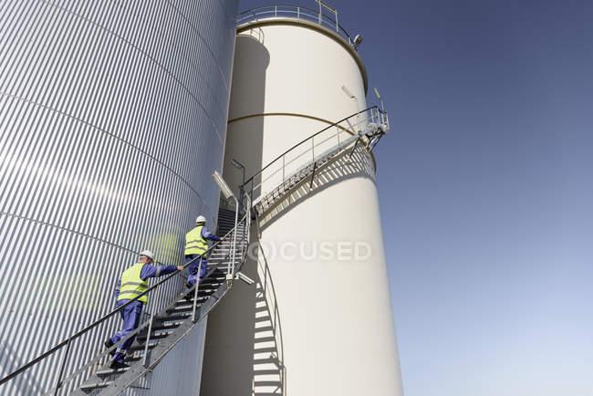 Trabalhadores escalando tanques de armazenamento de óleo na fábrica de mistura de óleo — Fotografia de Stock
