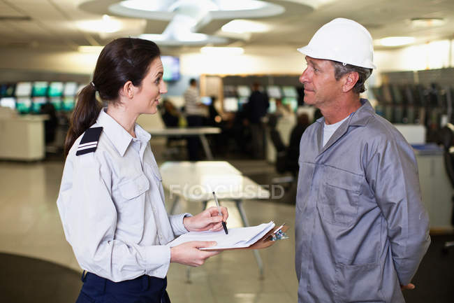Security personnel talking to worker — Stock Photo