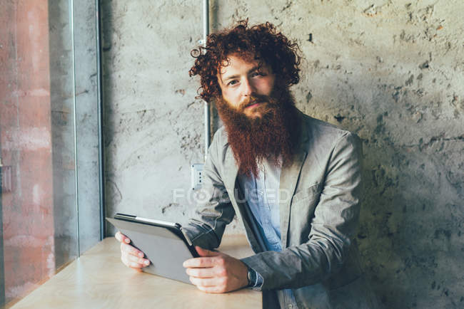 Portrait of young male hipster with curly red hair and beard in office — Stock Photo