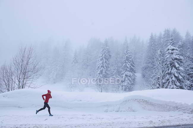 Боковий вид жінки біг в засніженій лісі, Гштаад, Швейцарія — стокове фото