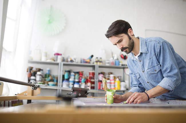 Impressora masculina aplicar tinta verde para serigrafia no studio de prensa — Fotografia de Stock