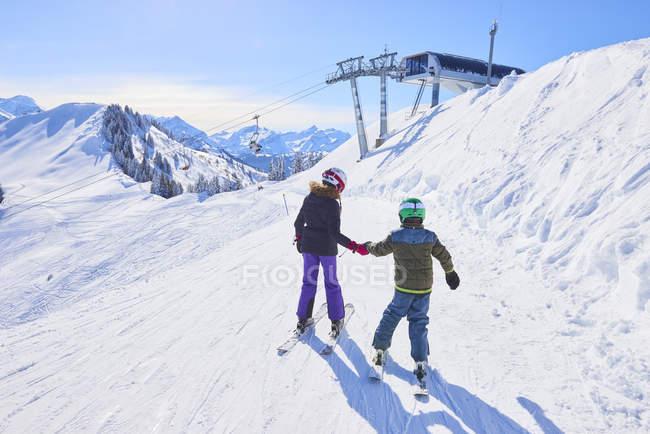 Задний вид девушки и брата, держащихся за руки на горнолыжном склоне, Гштаад, Швейцария — стоковое фото