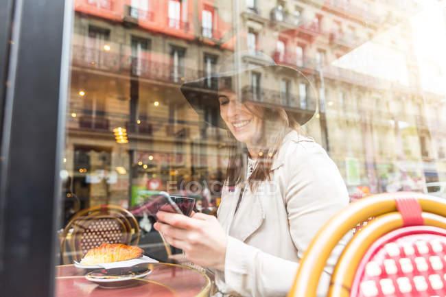 Vista finestra di giovane donna che legge smartphone in caffè, Parigi, Francia — Foto stock