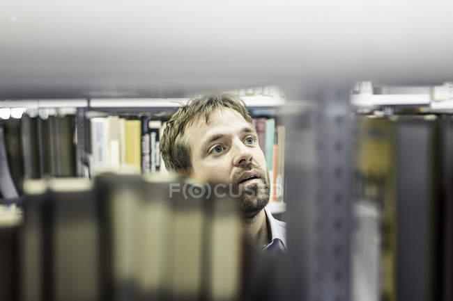 Homme d'affaires regardant des étagères de fichier dans la salle de magasin de bureau — Photo de stock