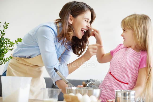 Мати і дочка випічки разом, морочити навколо — стокове фото