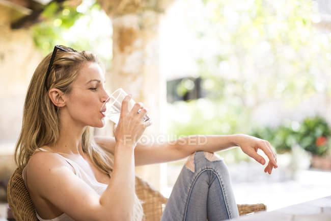 Молодая женщина отдыхает в саду патио питьевой воды — стоковое фото