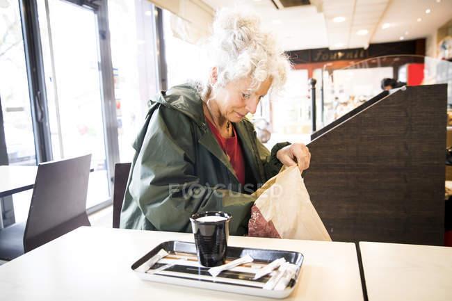 Mujer en cafetería buscando la bolsa de - foto de stock