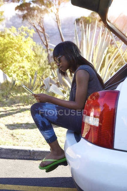 Young woman sitting in open car boot, looking at digital tablet — Stock Photo