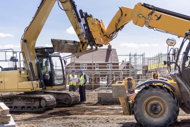 Строители с машины на сайте жилищного строительства — стоковое фото