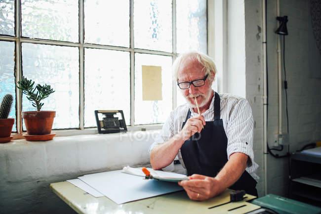 Artesano mayor sosteniendo lápiz y mirando el portapapeles en el taller de impresión - foto de stock