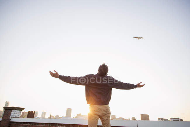 Человек на крыше с распростертыми объятиями — стоковое фото