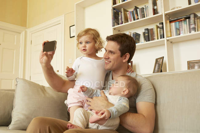 Mid adult man taking smartphone selfie with toddler and baby daughter on sofa — Stock Photo