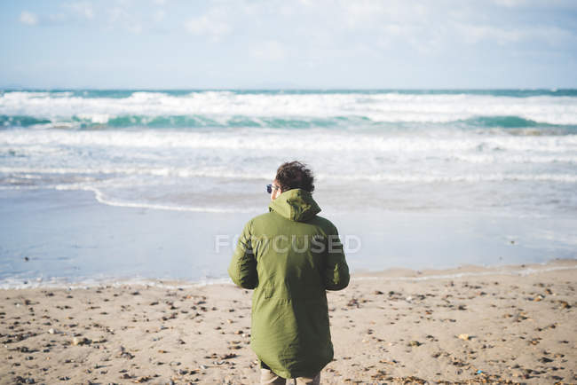 Rear view of man looking out to sea from windy beach, Sorso, Sassari, Sardinia, Italy — Stock Photo