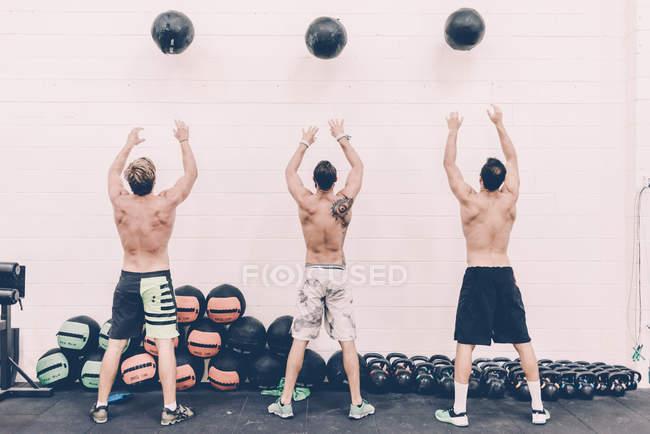 Задній вид три чоловіки хрест тренерів кидали кулі вправи в тренажерному залі — стокове фото