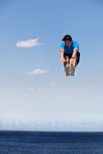 Hombre saltando de alegría sobre turbinas eólicas - foto de stock