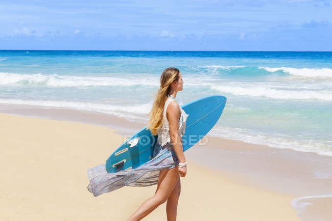 Young woman strolling on beach carrying surfboard, Dominican Republic, The Caribbean — Stock Photo