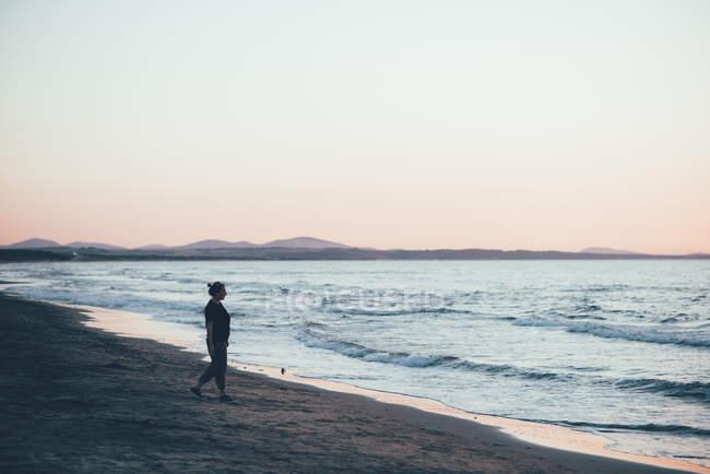 Женщина прогуливается по пляжу в сумерках, Сорсо, Сассари, Италия — стоковое фото