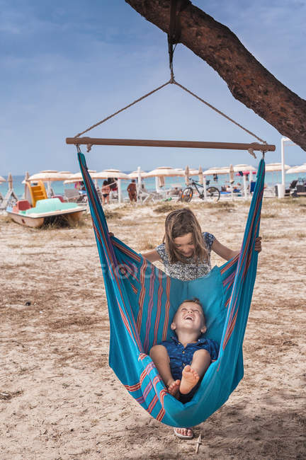 Fille pousser frère dans hamac sur la plage — Photo de stock