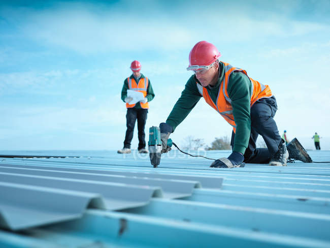 Building foreman reading plans insulates factory roof — Stock Photo