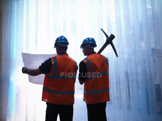 Silhouette of workers holding plans and a pickaxe - foto de stock