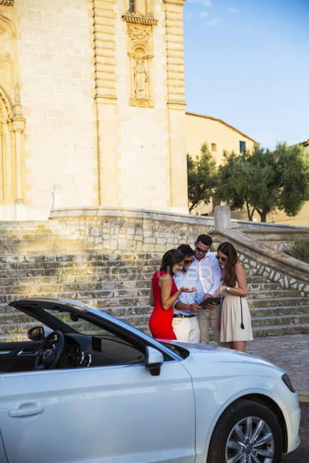 Due coppie di turisti guardando tablet digitale da chiesa, Calvia, Maiorca, Spagna — Foto stock