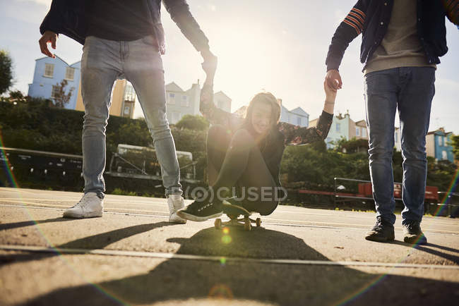 Three friends fooling around outdoors, young men pulling young woman along on skateboard, Bristol, UK — Stock Photo