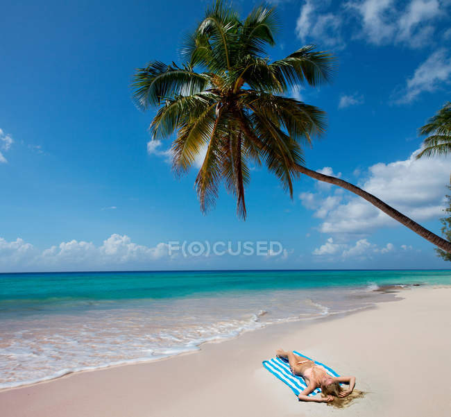 Жінка покладання на beach рушник — стокове фото