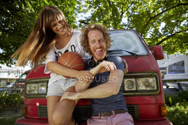 Giovani coppie che imbrogliano intorno all'aperto, ridendo, giovane donna che tiene basket — Foto stock
