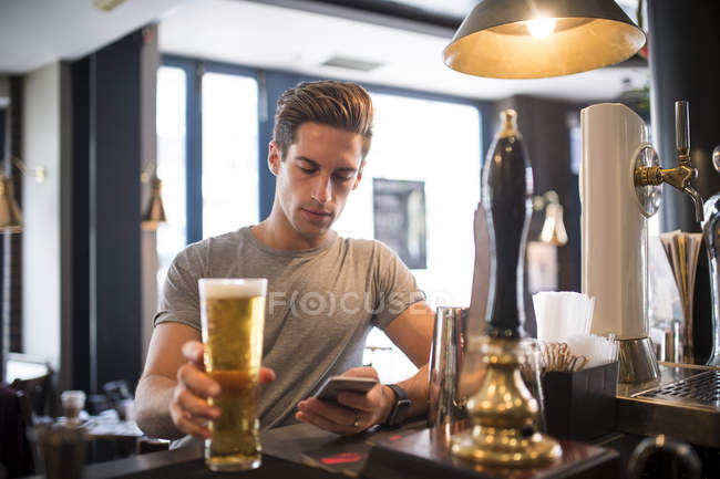 Молода людина читання смартфон в місті барі — стокове фото