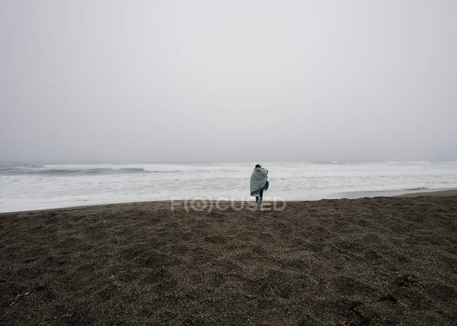 Young woman wrapped in blanket walking on misty beach — Stock Photo