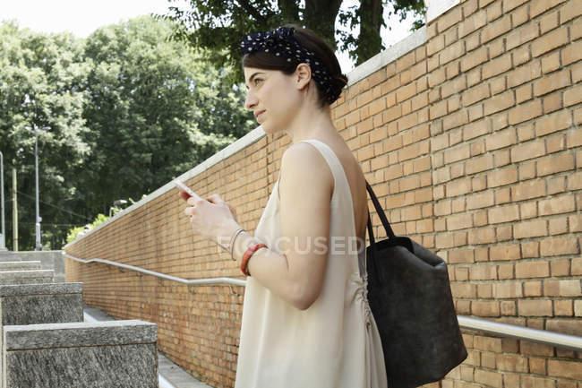 Стильная женщина, использующая смартфон, глядя вдаль на улице, Милан, Италия — стоковое фото