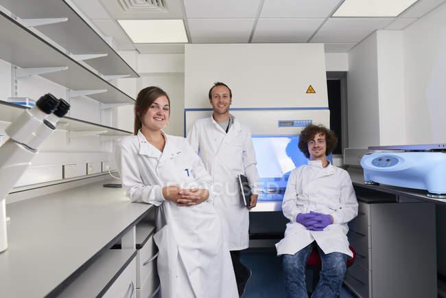 Науковці в лабораторії, які дивляться на камеру посміхаючись — стокове фото