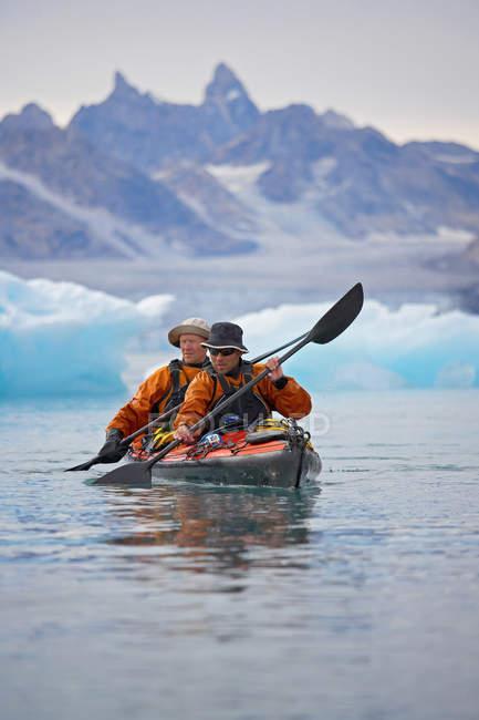 Canoa de enfileiramento dos homens no mar glacial imóvel — Fotografia de Stock