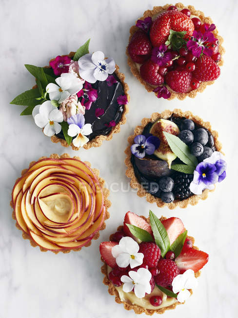 Top view of various tarts with fruit and flowers — Stock Photo