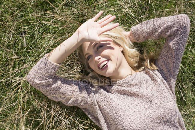 Jovem mulher deitada na grama, protegendo os olhos do sol — Fotografia de Stock