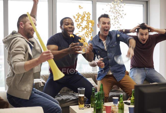 Grupo de hombres viendo el evento deportivo en la televisión celebrando - foto de stock