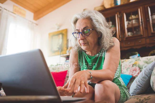 Donna sul divano utilizzando il computer portatile a casa — Foto stock
