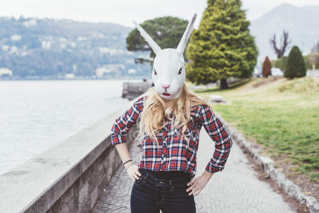 Portrait of woman wearing rabbit mask with hands on hips, Lake Como, Italy — Stock Photo