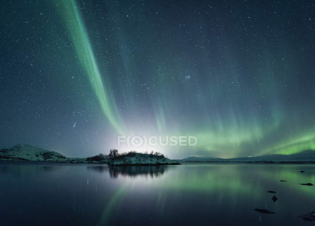 Starry sky illuminated with Northern Lights reflecting in water — Stock Photo